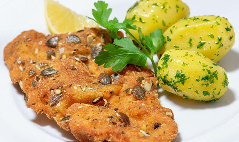 Putenschnitzel im Kürbismantel mit Petersilerdäpfel