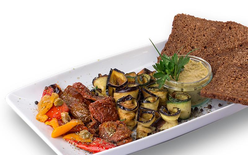 Antipastiteller mit Tapenade, eingelegtem Gemüse und Mischbrot